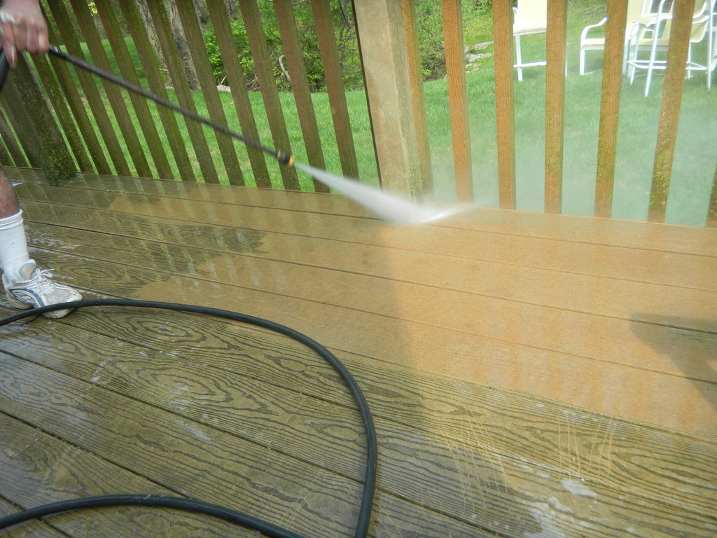 A homeowner cleaning the deck using a pressure washer and reaping immediate results