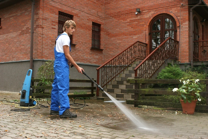 A man cleaning the driveway with a pressure washer