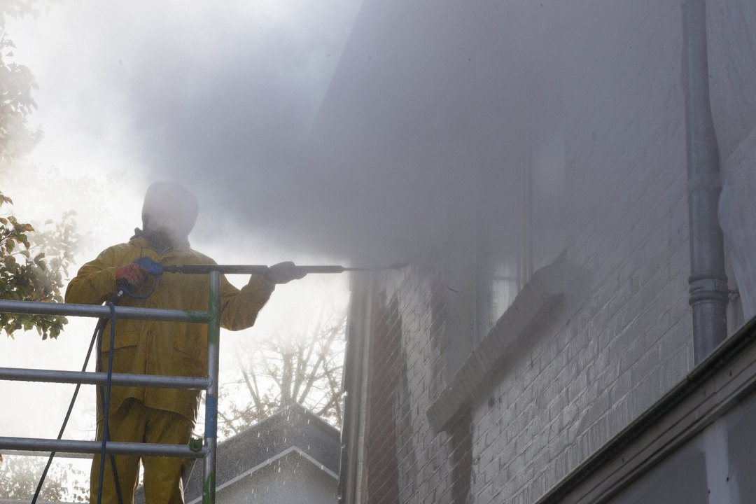 A man using pressure washer to clean the brick wall of the house