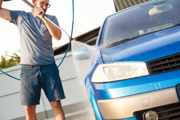 A man pressure washes a luxury car