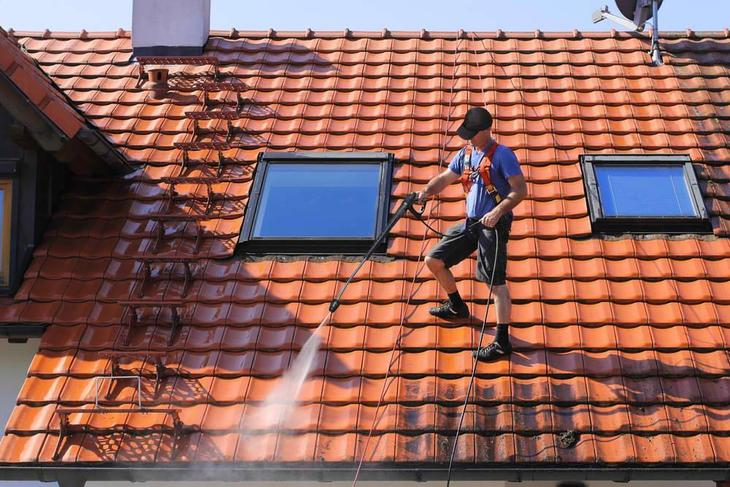 Man is cleaning his metal roof with his high-pressure washing cleaner
