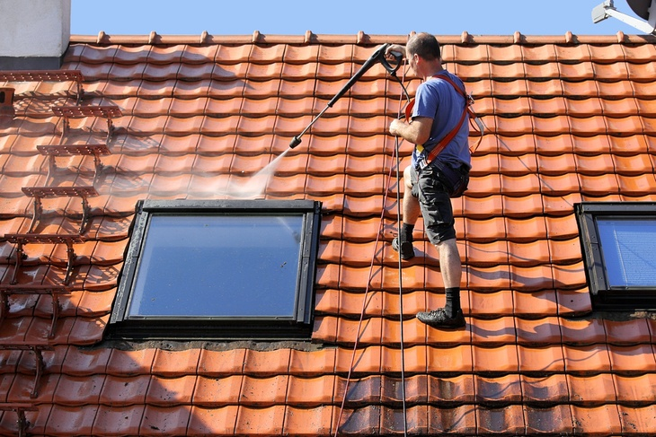 Man on top of his metal red roof using a high powered pressure washer to clean it