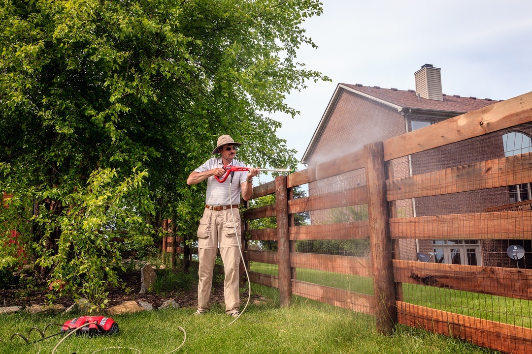 A man using cold water pressure washer to clean wooden fence