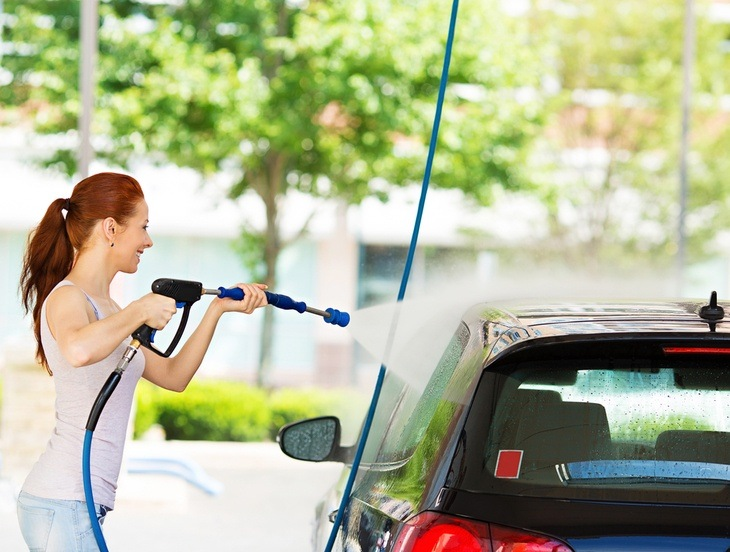 A woman pressure washes her car