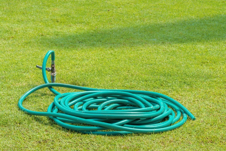 Color green and blue watering hose coiled up and wrapped