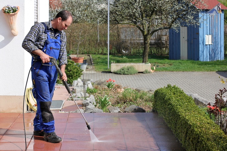 Man cleaning his terrace with his high powered pressure washerMan cleaning his terrace with his high powered pressure washer