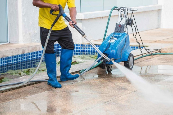 Man making use of a high-powered pressure washer to clean his porch