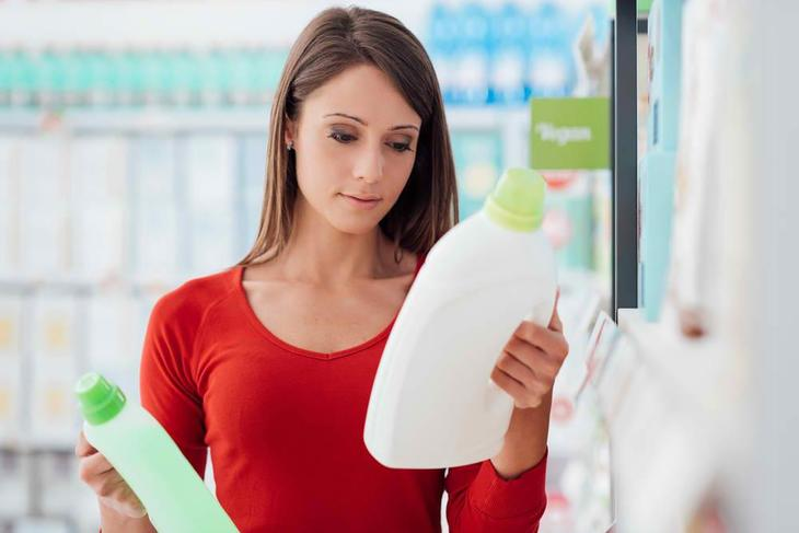 Woman checks out which of the detergents to choose from